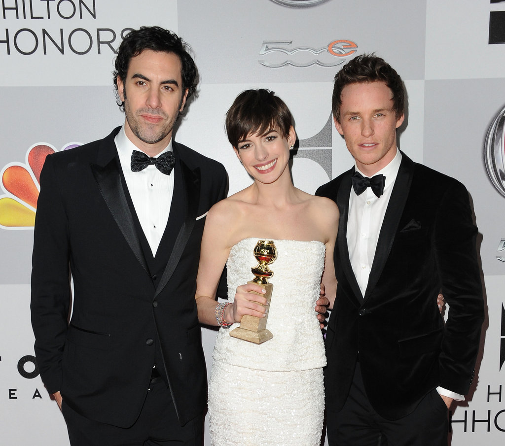 Anne Hathaway posed with Eddie Redmayne, Sacha Baron Cohen, and her Golden Globe.