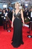 Jane Lynch went edgy in a black leather bodice with pleated skirt gown, textured clutch, and gold hoops.