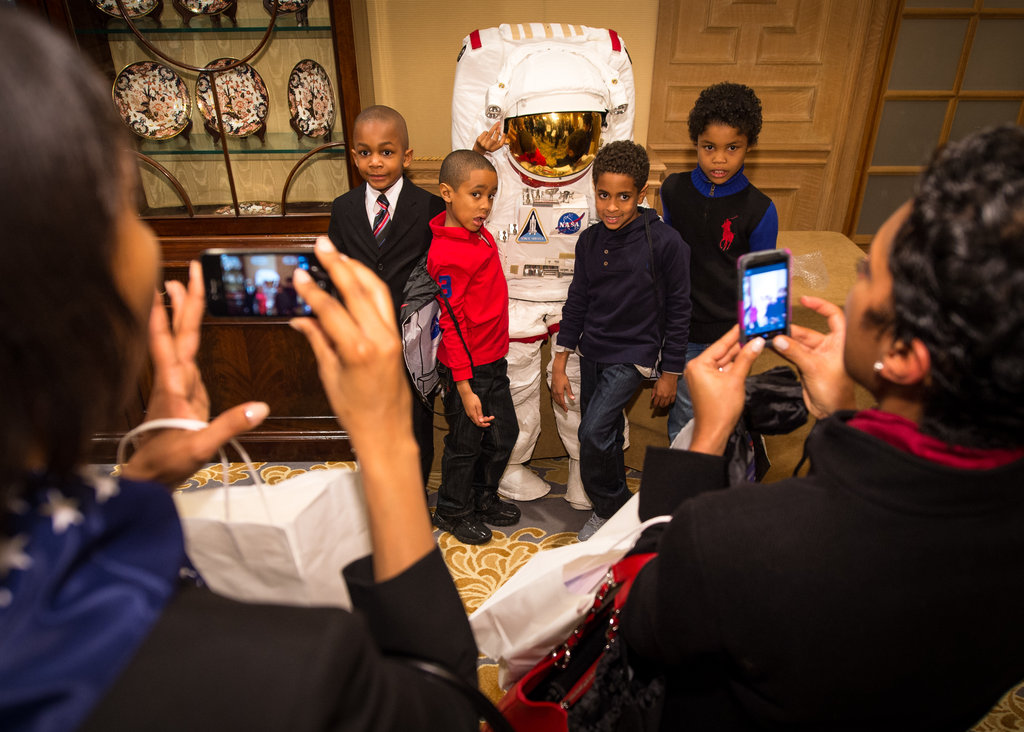 School boys pose with a child-size spacesuit during the STEM education event NASA held inauguration weekend. Source: Flickr User NASA HQ