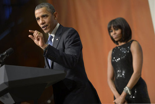 Even in the background, Michelle shines, especially with a little help from this black shimmery Michael Kors gown.