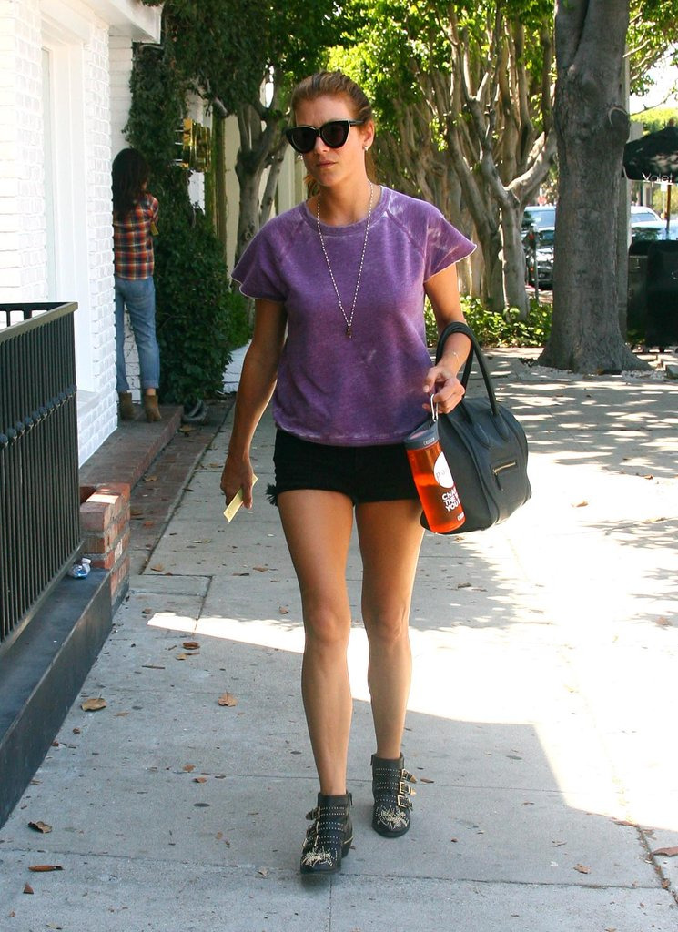 Kate Walsh showed a little leg in black denim cutoffs, a purple shortsleeve raglan top, and black studded Chloé boots.