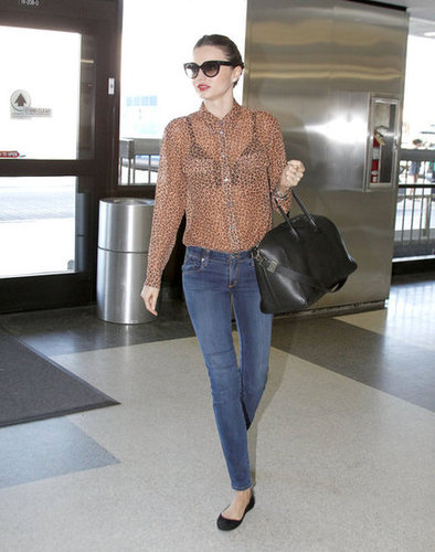 Miranda Kerr showed off sexy travel style in an Equipment sheer leopard blouse with skinny jeans and ballet flats.