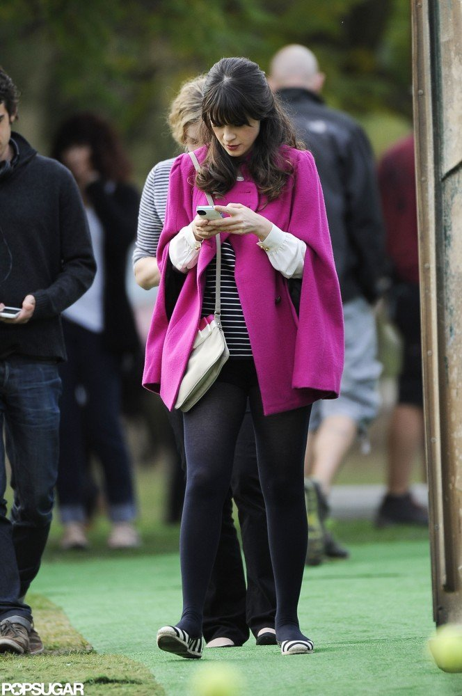 Zooey Deschanel attended to her phone while on set.