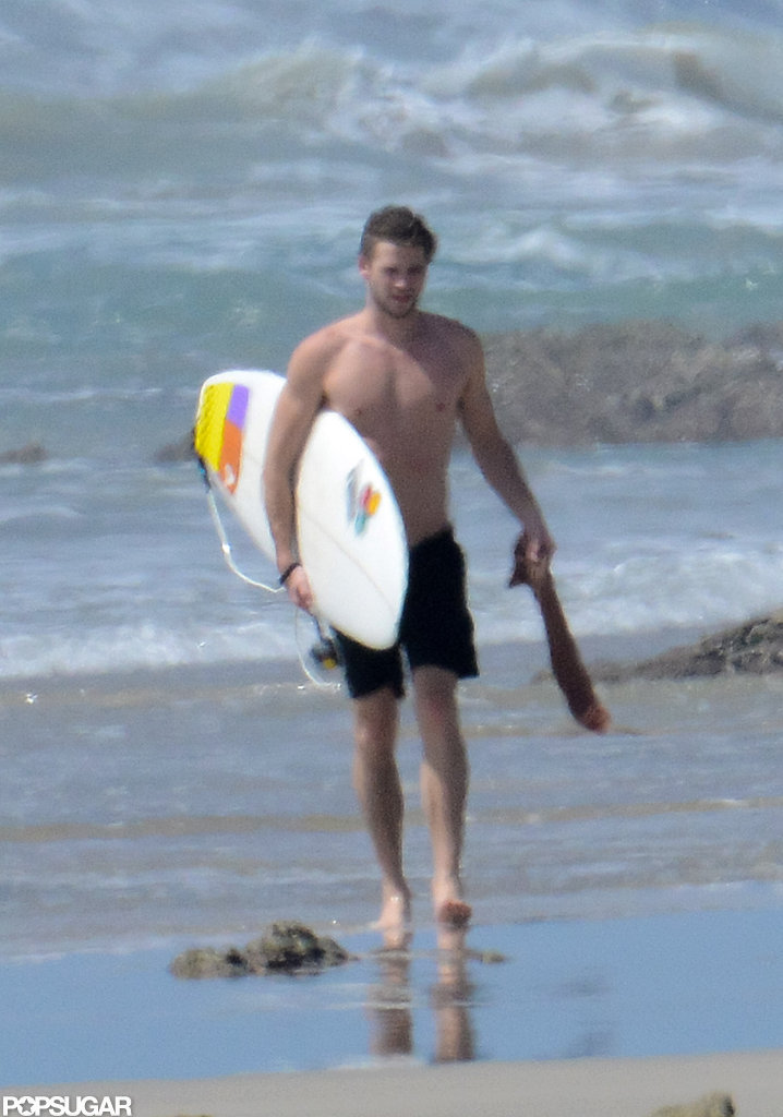 Liam Hemsworth walked in the sand.
