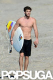 Liam Hemsworth carried his surfboard on the beach in Costa Rica in January.