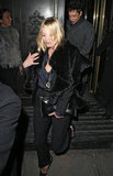 Kate Moss took her monochromatic London look —silk blouse, cropped trousers, and sateen-finished blazer — to new heights with a plush fur wrap and a crocodile envelope clutch.