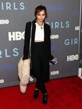 Zoe Kravitz showed off her punky Winter style in black high-waist trousers, a white crop top, a long black coat, lace-up booties, and a fur collar in her hand.