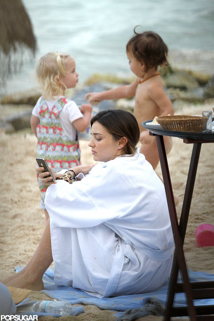 Miranda Kerr relaxed on the beach in a bathrobe.