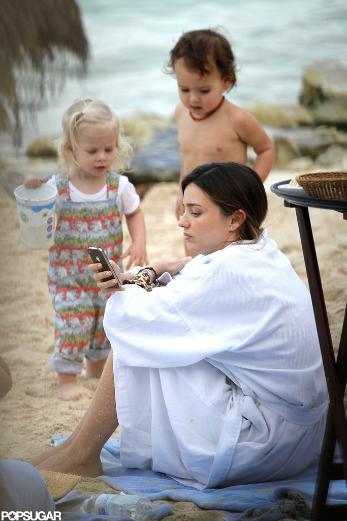 Miranda Kerr checked her phone while wrapping up in a robe beachside.