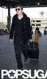 Brad Pitt wore sunglasses as he wheeled his luggage.