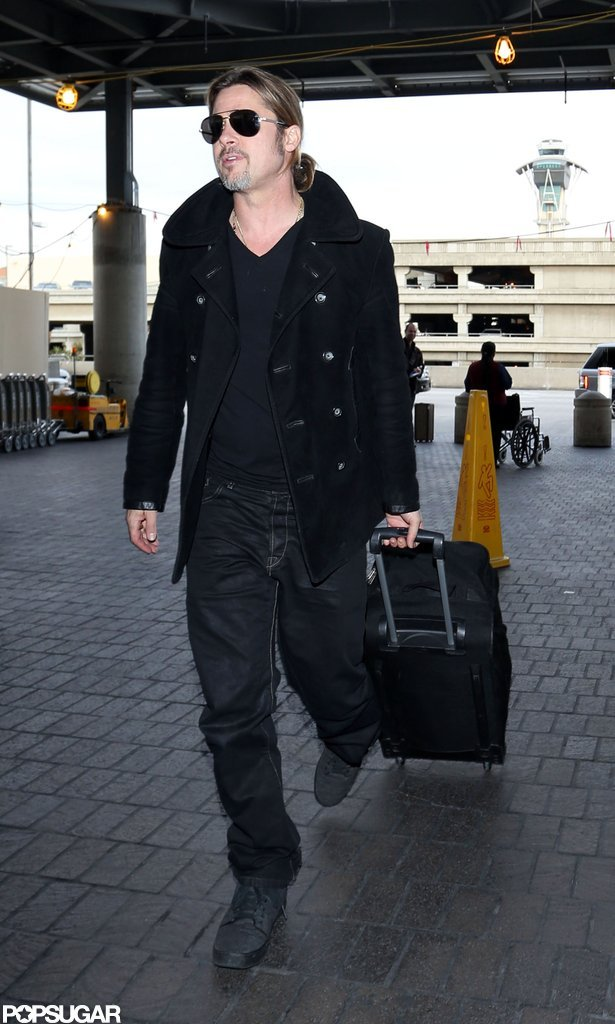 Brad Pitt wore sunglasses as he wheeled his luggage.