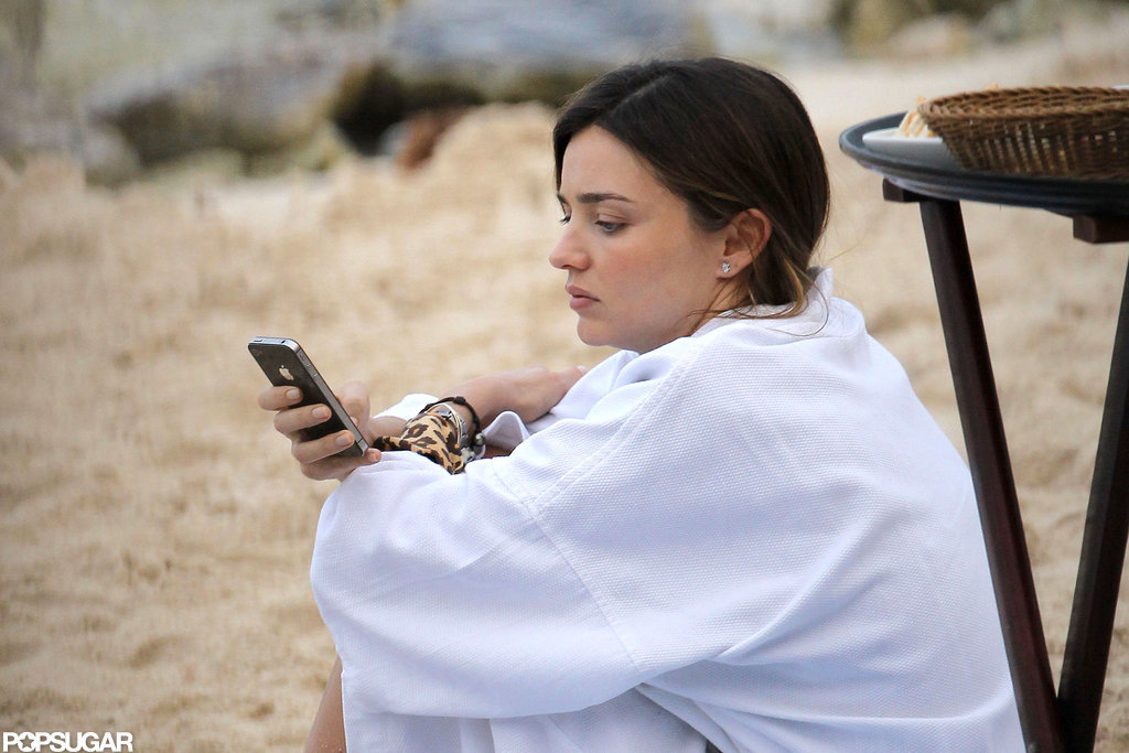 Miranda Kerr checked her phone on the beach.