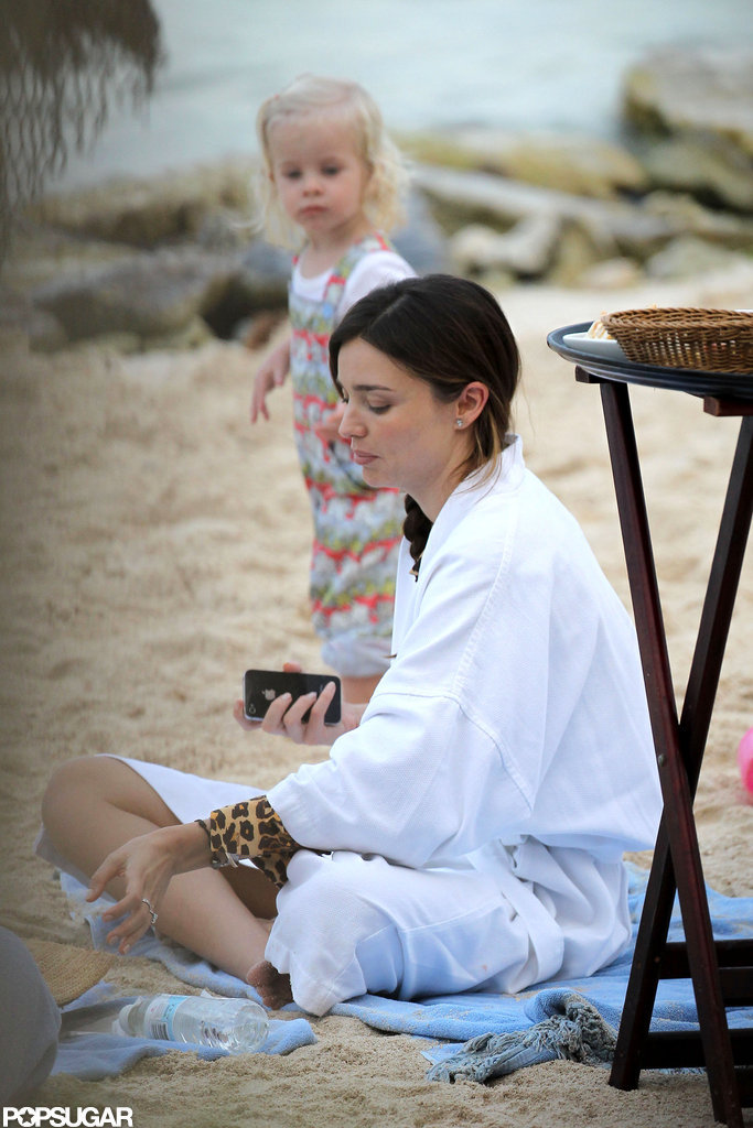 Miranda Kerr took a break from the sun and rested in the sand.