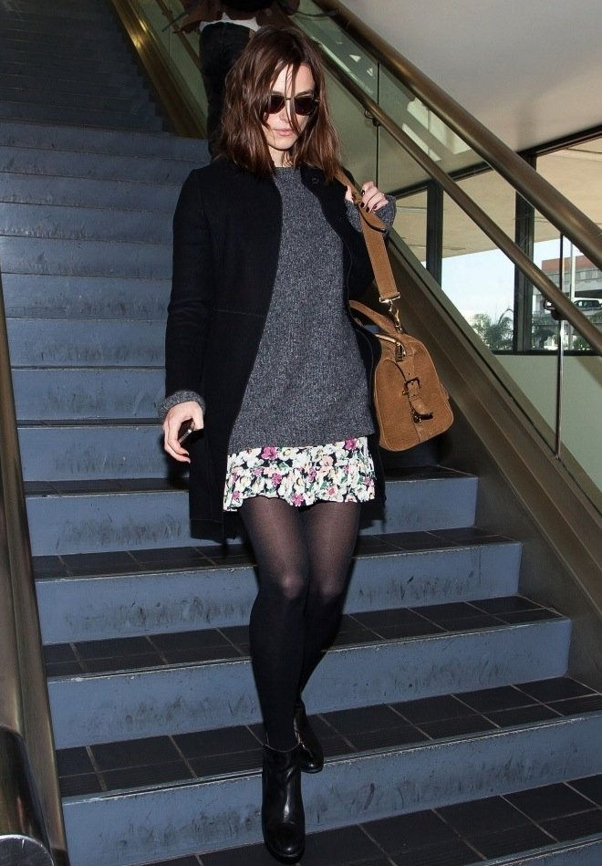 Keira Knightley styled a sweet floral-print skirt with cozy separates: a gray sweater, black coat, and black booties.