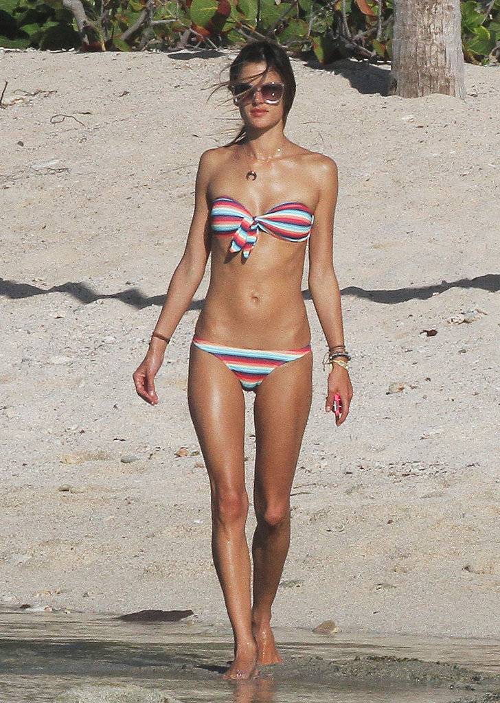 Alessandra Ambrosio sported a striped bikini as she strolled on the beach solo Wednesday.