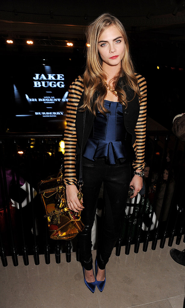 Cara Delevingne elevated the dress code at the Burberry Acoustic Presents event in London by donning a stripe-sleeved varsity jacket and a navy satin Burberry bustier with black leather pants and sapphire satin pumps. The blonde stunner accessorised her party style with a fox link necklace and a stunning gold mirrored satchel, both by Burberry.