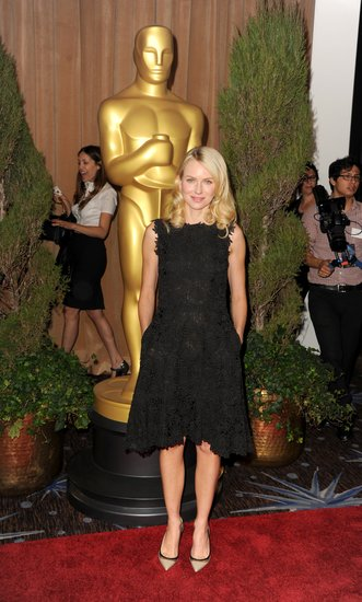 Naomi Watts selected a feminine black embroidered fit-and-flare Valentino sheath and perfected the luncheon ensemble with a pair of ladylike Christian Louboutin black-trimmed pointed-toe pumps.