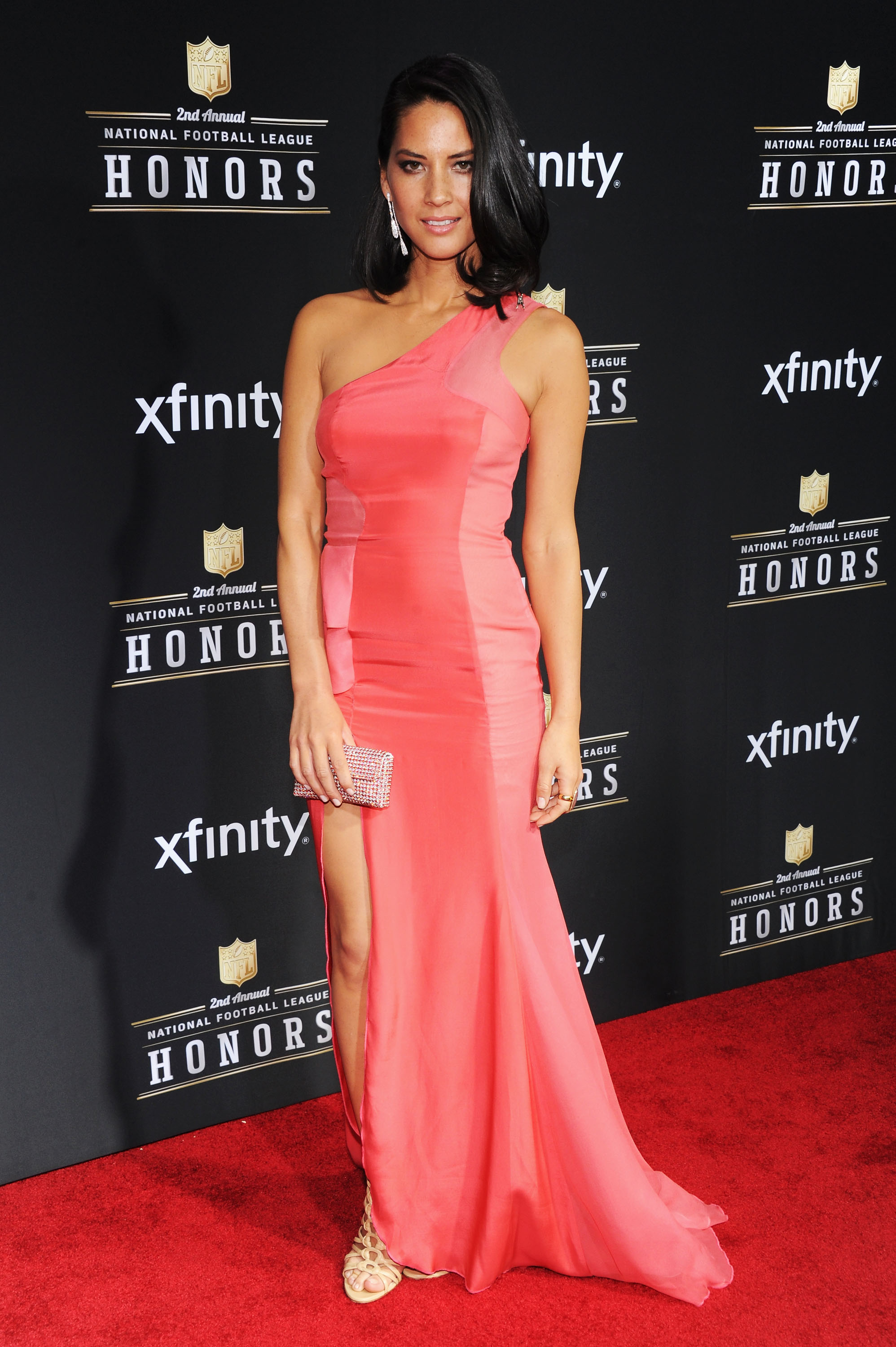 For the NFL Honors award show, Olivia stepped out in a bright — albeit glamorous — coral-hued one-shoulder gown by Izmaylova, complete with a sexy thigh-high split, then finished off the floor-length look with strappy nude heels.