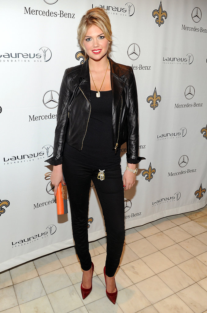 Kate Upton partnered her all-black look with a long pendant necklace, orange clutch, and red pointy-toe pumps at the Mercedes-Benz/Laureus event.