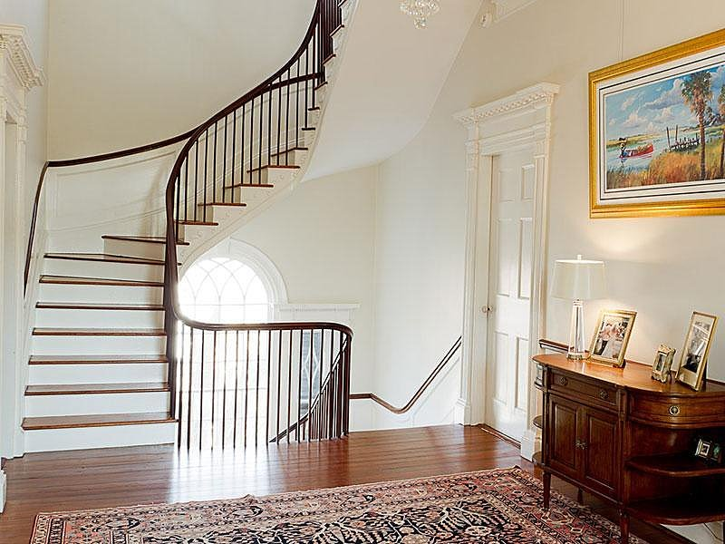 Noah and Allie couldn't keep their hands off each other that first day, and they barely made it up the stairwell. In this home, the landing area is accented with a patterned rug, a traditional wooden chest, and a cool, unexpectedly modern lamp. Source: Sotheby's
