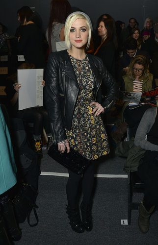 Ashlee Simpson topped her printed dress with a black leather biker jacket, then completed her front-row look with a gray beanie at Nicole Miller.