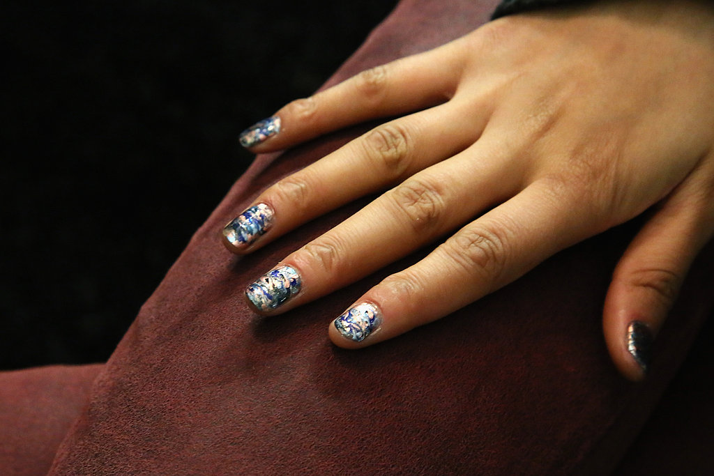 "Lead manicurist Michelle Saunders for Essie created the oil-slicked nail design. ""Rebecca Minkoff said that she wanted the nails to have an oil-slick effect, which was inspired by her handbags in the collection,"" she said."