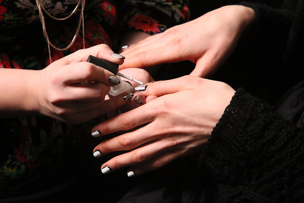 "The nails were designed by Simcha Whitehill for Color Club. She brought to life a ""picture frame"" manicure for a simple and graphic result. To create the look, she painted the base colour first (in this case, the black shade first). Then she painted the centre white, leaving the perimeter black."