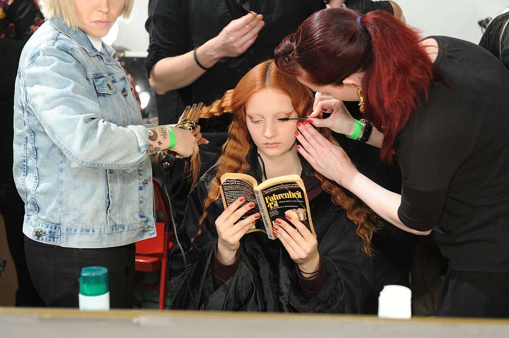 A model read Fahrenheit 451 while getting primped backstage at the Creatures of the Wind Fall 2013 fashion show during Mercedes-Benz Fashion Week in New York.