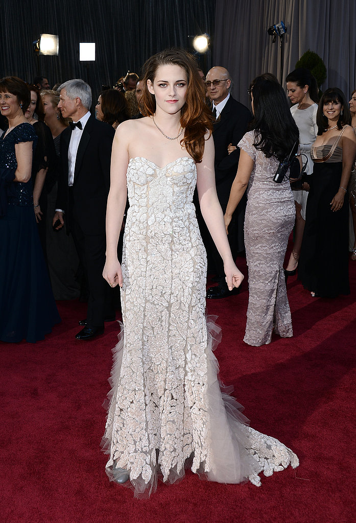 Kristen Stewart donned a pale blush Reem Acra gown featuring intricate lace detailing.
