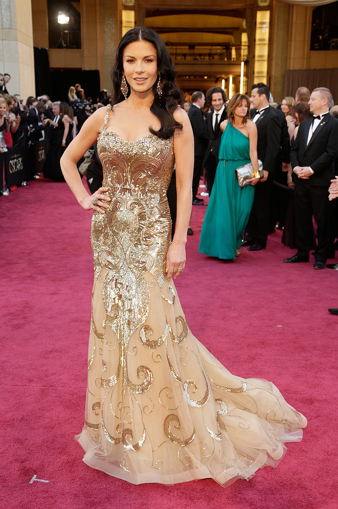 Catherine Zeta-Jones shined in a golden Zuhair Murad gown featuring intricate metallic beadwork and sheer panels.