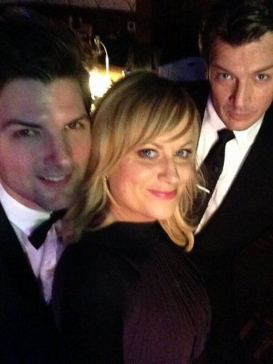 Nathan Fillion got cozy with Parks and Recreation's Adam Scott and Amy Poehler. Source: Twitter user NathanFillion