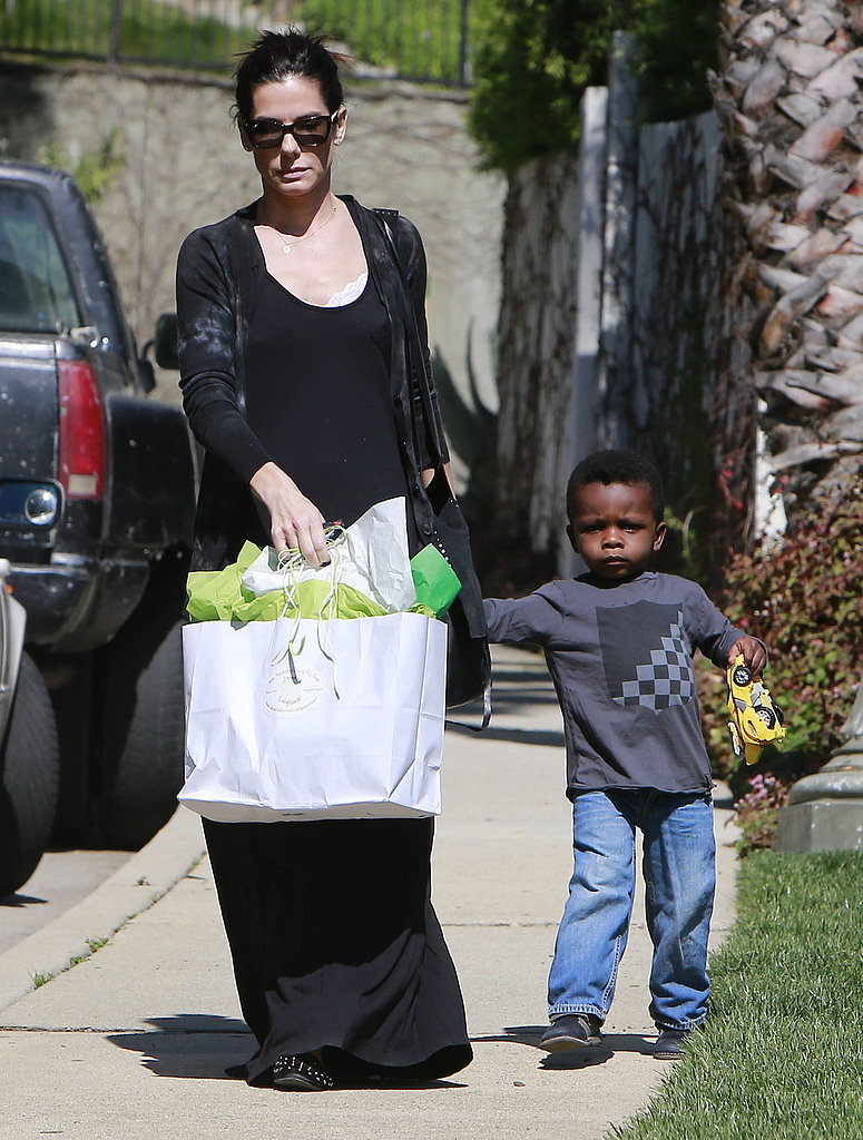 Sandra Bullock took little Louis by the hand on the way to Charlize Theron's Beverly Hills home for her son Jackson's birthday party.