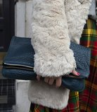 A textural fold-over clutch was paired with a fur coat and plaid trousers for a lesson in Winter layers.
