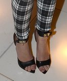 At a pre-Oscar party in West Hollywood, Miley Cyrus completed her plaid pants via black ankle-strap Givenchy sandals.