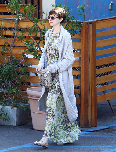 Anne Hathaway was feminine and relaxed in a floral maxi dress from Madewell, a long Autumn Cashmere cardigan, her python-print Stella McCartney bag, metallic sandals, and clear sunglasses while out and about in LA.