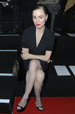 Melissa George sat front row at Nina Ricci wearing all black — a skirt-suit with fishnet tights and cut-out pumps — with a pop of hot-pink lipstick.