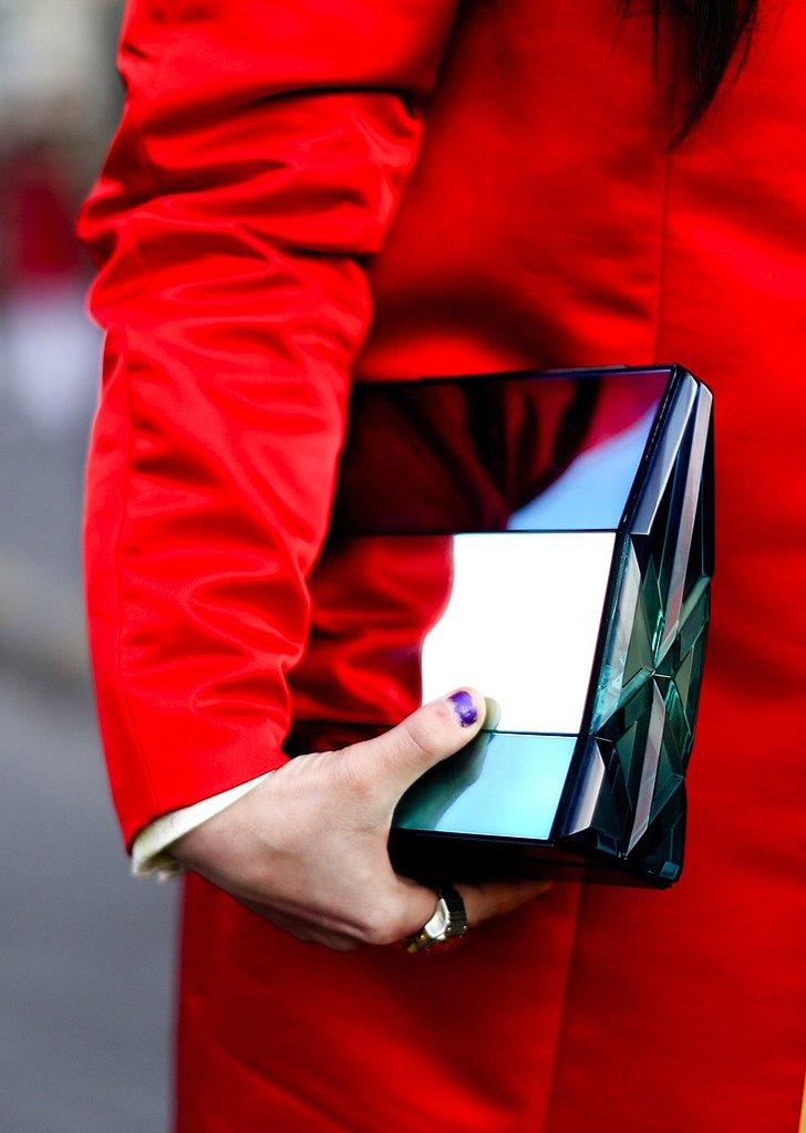 A reflective structured clutch shined against a red coat.