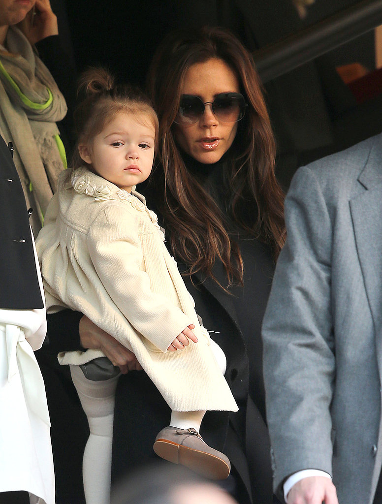 Victoria Beckham held her daughter, Harper, as they cheered on dad David Beckham during a soccer match in Paris.