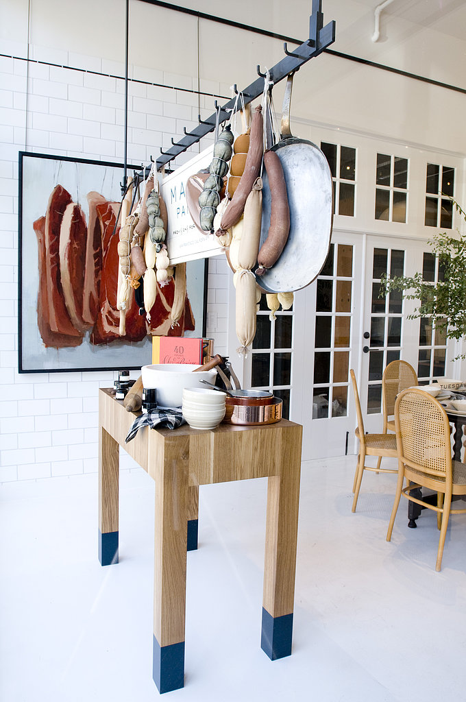 Utilize racks to hang more than just pots and pans. While you may not have ropes of sausage and dried salamis at the ready, things like potted herbs and sacks of garlic would achieve the same rustic culinary feel.   Photo courtesy of Angie Silvy