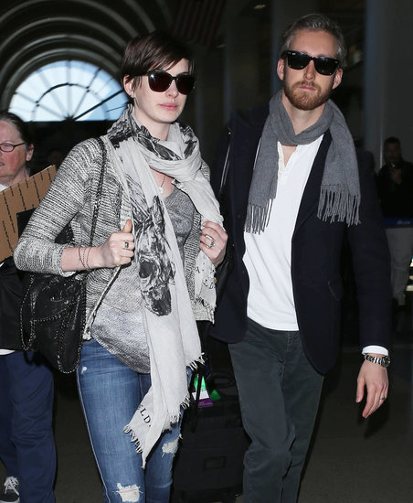 Anne Hathaway and Adam Shulman both covered up with scarves for their trip back to the West Coast on Wednesday.