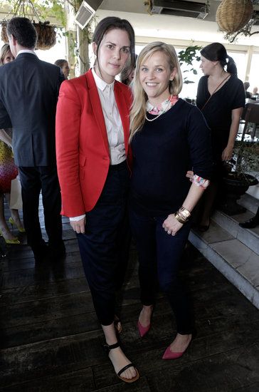 Reese Witherspoon posed with stylist Leslie Fremar in a more casual ensemble: a floral blouse topped with a black sweater, finished with a pearl necklace and pink pumps.