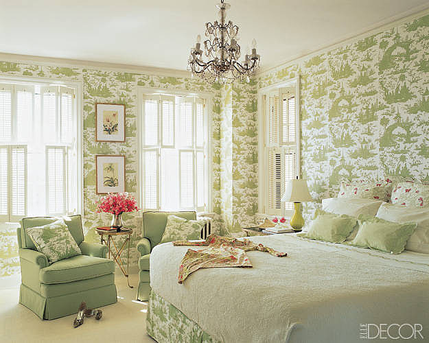 Green is the theme of this master bedroom. Toile wallpaper and light green textures create an airy ambience, while antiques add charm and slight pops of pink offer a burst of energy.  Source: Elle Decor