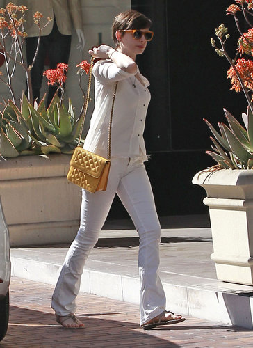 Anne Hathaway showed off her lighter side with white jeans, an ivory blouse, and her yellow quilted Stella McCartney bag.