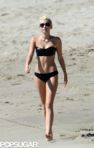 When she took off her polka-dot dress, Miley revealed a sexy black bikini with a leather-like sheen.