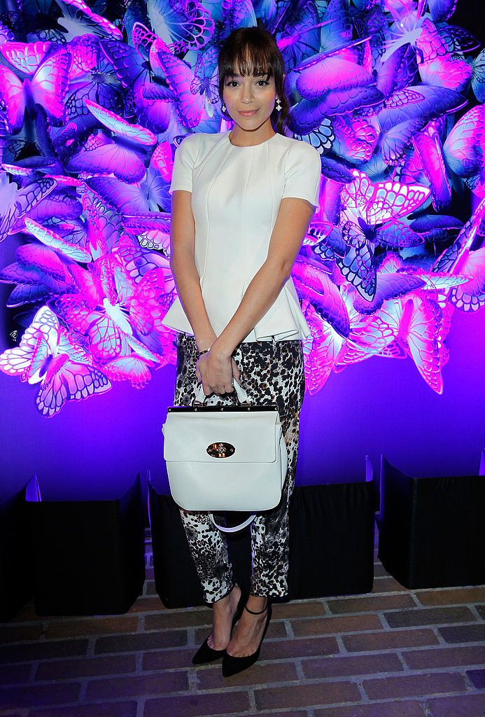 At the Mulberry Fall 2013 dinner in LA, Ashley Madekwe looked feminine and funky in a white peplum top, printed trousers, black ankle-strap Monika Chiang pumps, and a white Mulberry bag.