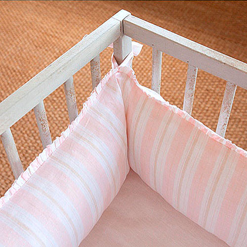 Keep your little one snug as a bug while they sleep with this pretty pink striped crib bumper ($220).