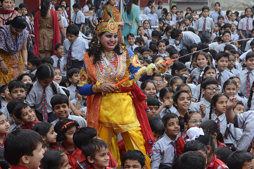A school teacher dressed as Lord Krishna used a water gun during Holi celebrations at Shri Ram Ashram Public School in Amritsar, India.