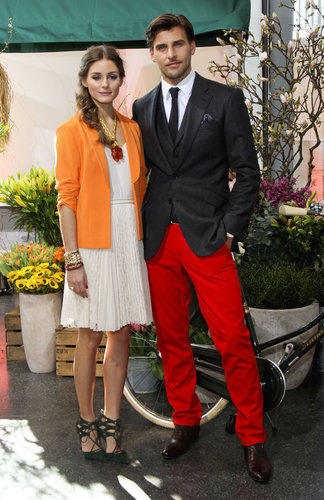 With nods to Spring, Olivia outfitted a sweet, pleated day dress with a bright tangerine-hued jacket and coral jewels then finished the look with a pair of lace-up heels for a presentation in Hamburg, alongside beau Johannes Huebl.
