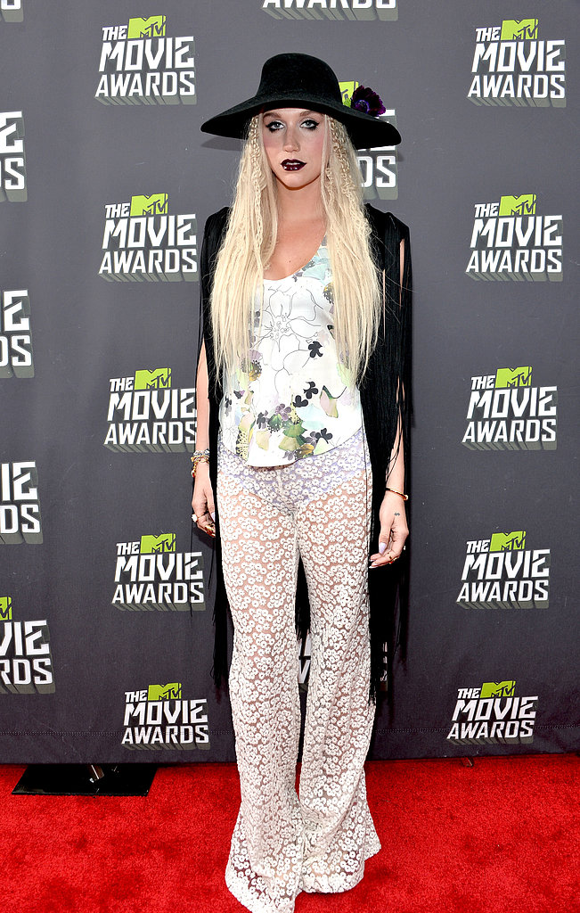 Ke$ha kept it off-kilter per usual in sheer printed trousers, a floral tank, a black fringe vest, and a black wide-brim hat.