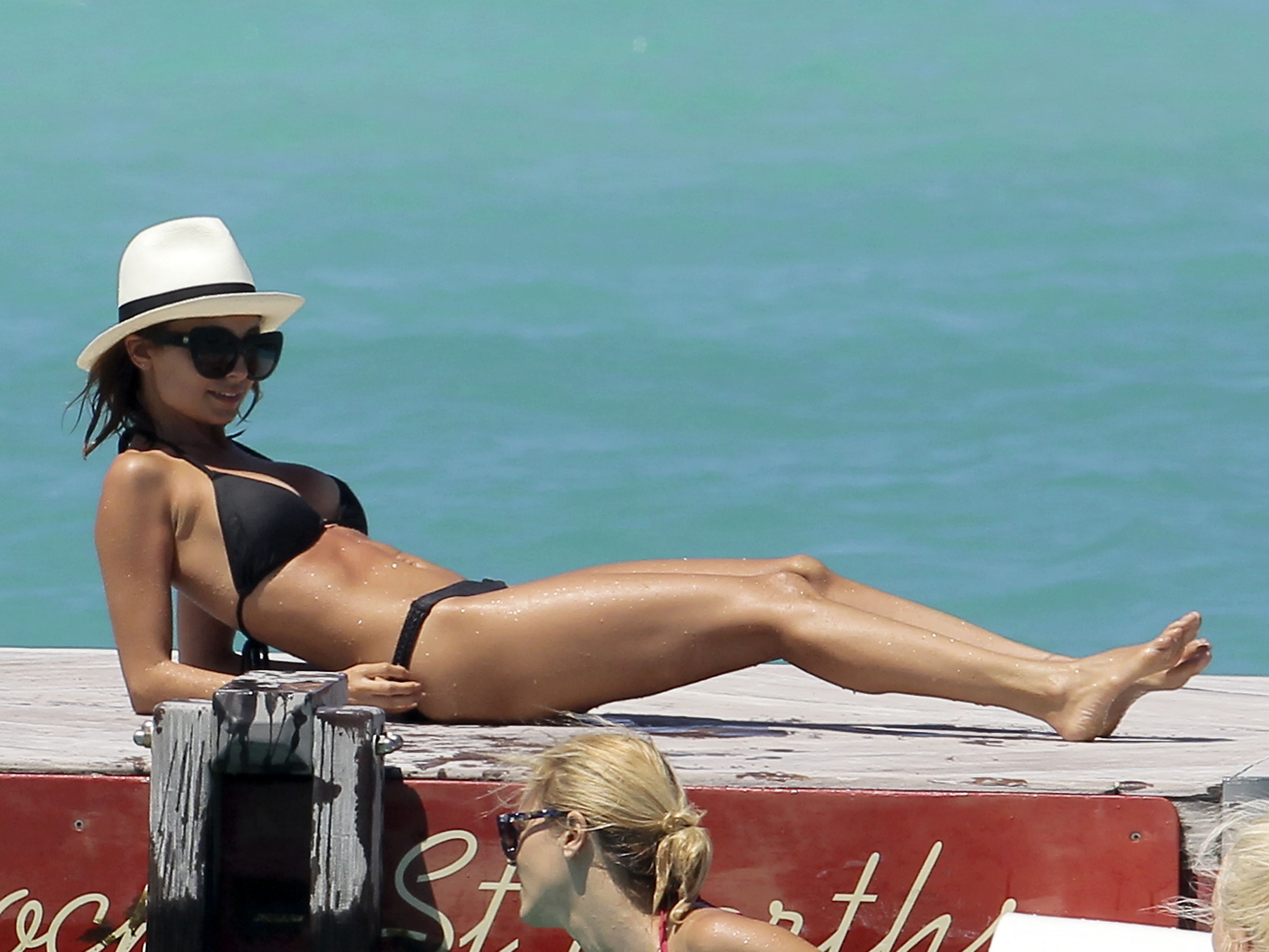 Nicole Richie lounged in St. Barts in April wearing a black triangle bikini, House of Harlow cat-eye sunglasses, and a crisp white fedora.